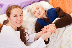 Caregiver accompanying a senior in bed