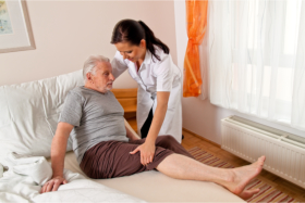 Nurse assisting a senior in bed