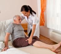 Assisting elder male in bed